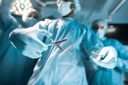 Photo for Bottom view of multicultural surgeons with medical tools - Royalty Free Image
