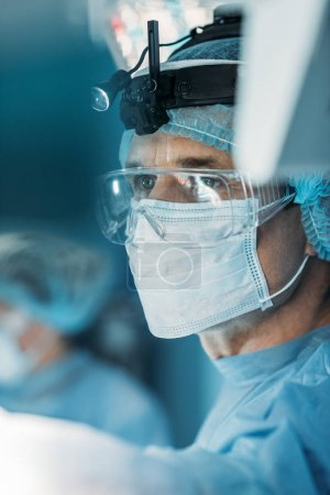 handsome surgeon in medical mask looking away