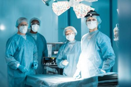four multicultural doctors looking at camera in operating room
