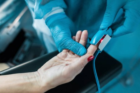 cropped image of doctor wearing pulse oximeter on patient finger in operating room