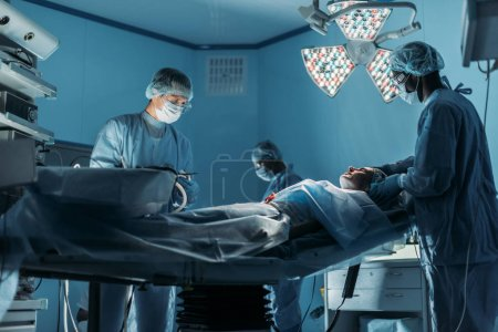 multicultural doctors preparing patient for surgery in operating room
