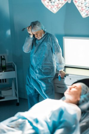 exhausted doctor standing near patient in surgery room