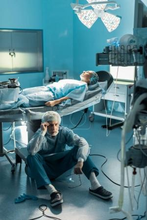 doctor sitting on floor near patient on operating table