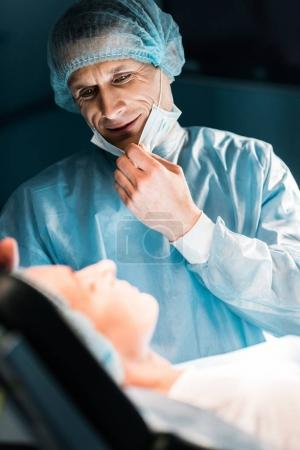 smiling doctor looking at patient in surgery room