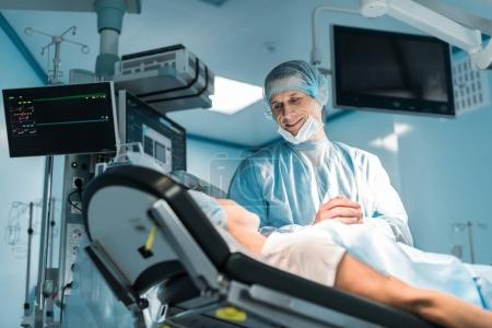 bottom view of smiling doctor and patient holding hands in operating room