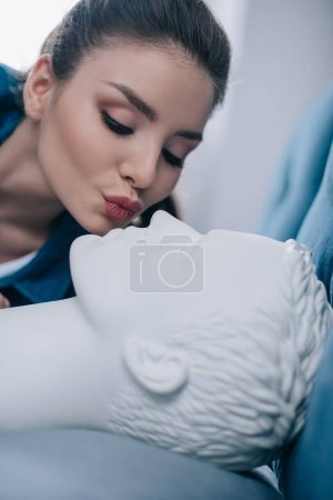 close up view of woman kissing mannequin in bed, one way love concept