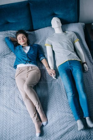Photo pour Jeune femme au lit avec mannequin, concept de rêve de relation parfaite - image libre de droit