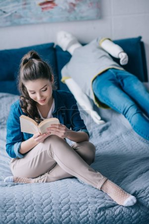 woman reading book while resting on bed with mannequin, loneliness concept