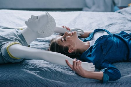 Photo for Side view of smiling woman and mannequin lying on bed, loneliness concept - Royalty Free Image