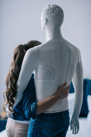 Photo pour Vue arrière du femme étreignant poupée profane, concept de rêve de relation parfaite - image libre de droit