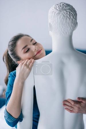 Photo pour Souriante jeune femme étreignant poupée profane, une façon aime concept - image libre de droit