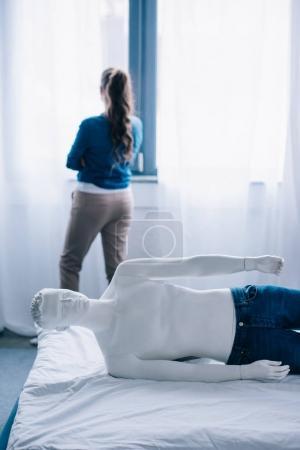 Photo pour Vue arrière du femme debout à la fenêtre et profane poupée allongé sur le lit, la notion de solitude - image libre de droit