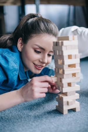 selective focus of woman playing blocks wood game with layman doll near by at home, perfect relationship dream concept