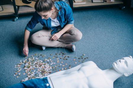 woman playing with puzzles with manikin near by, perfect relationship dream concept