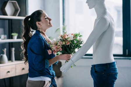 young woman pretending to receive flowers from layman doll, perfect relationship dream concept