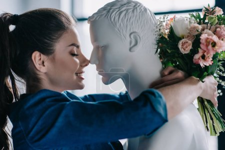 Photo for Side view of smiling woman with flowers hugging mannequin, perfect man dream concept - Royalty Free Image
