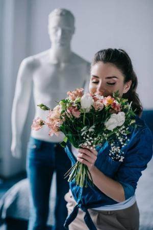 Photo pour Mise au point sélective de la jeune femme avec bouquet de fleurs et mannequin derrière, une façon aime concept - image libre de droit