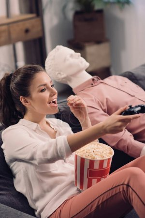 side view of woman eating popcorn while playing video game with manikin near by, loneliness concept