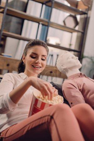 Photo pour Jeune femme mangeant popcorn avec mannequin près par, sens unique amour concept - image libre de droit