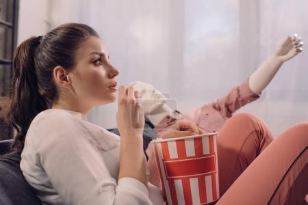 Photo pour Femme, manger des pop corn tout en regardant le film avec le mannequin à la maison, le concept de rêve de relation parfaite - image libre de droit