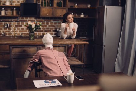 selective focus of young woman with cup of coffee and manikin at table in kitchen, perfect relationship dream concept