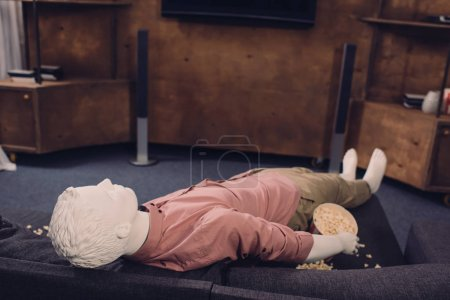 layman doll in casual clothes lying on sofa with popcorn