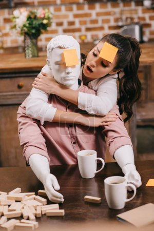 portrait of woman with sticky note on forehead hugging layman doll at home, perfect relationship dream concept