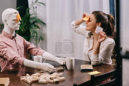 Photo pour Jeune femme jeu avec poupée profane à table avec les tasses de café, concept de solitude - image libre de droit