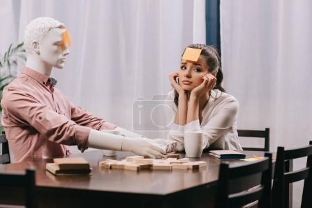 Photo pour Jeune femme triste pense-bête sur front assis à table avec mannequin, notion de solitude - image libre de droit