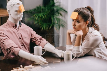 sad young woman with sticky note on forehead sitting at table with mannequin, loneliness concept