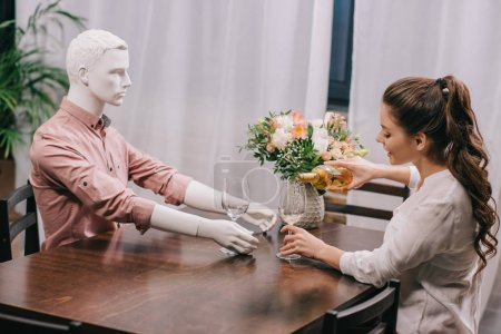 Photo for Woman pouring wine into glass while sitting at table with layman doll, unrequited love concept - Royalty Free Image