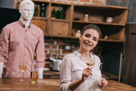 selective focus of woman with glass of wine and manikin in casual clothing in kitchen at home, unrequited love concept