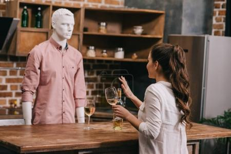 Photo for Woman with glass of wine and manikin in casual clothing in kitchen at home, unrequited love concept - Royalty Free Image