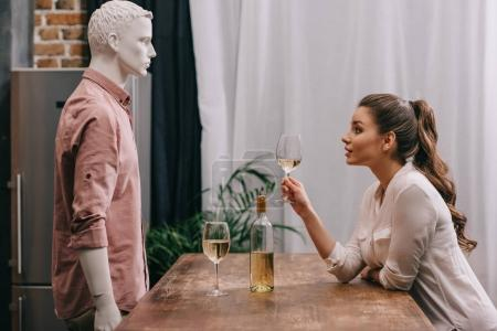 Photo for Side view of young woman with glass of wine at table with male manikin, unrequited love concept - Royalty Free Image