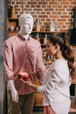 young woman pretending to except gift from mannikin, loneliness and perfect man dream concept