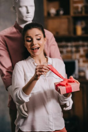 excited woman opening gift in hands with manikkin hugging her behind, perfect man dream concept