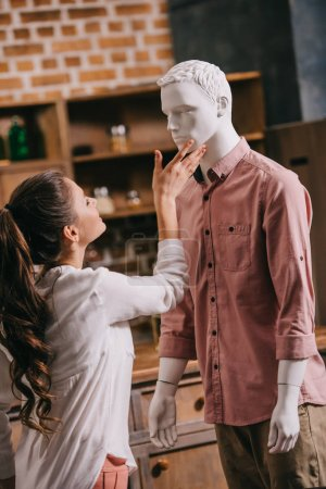 side view of woman touching mannequin in casual clothing, one way love concept