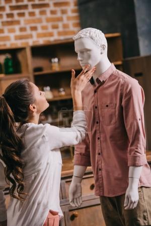 Photo pour Vue de côté de femme toucher mannequin dans des vêtements tout-aller, aller simple amour concept - image libre de droit