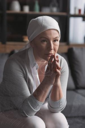 upset sick mature woman in kerchief sitting and looking away, cancer concept