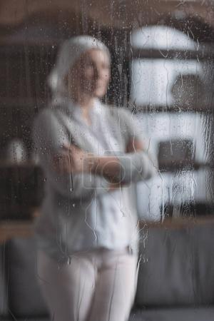 close-up view of glass with raindrops and sick mature woman standing behind