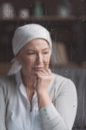 sick mature woman in kerchief crying behind window with raindrops