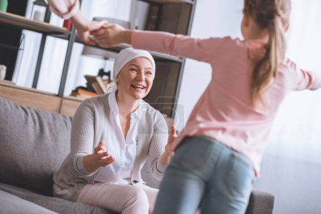 Photo for Happy sick grandmother in kerchief looking at cute little granddaughter - Royalty Free Image