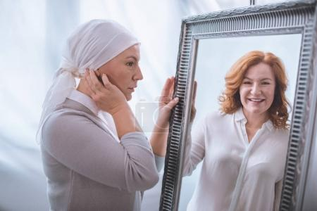 Photo for Upset sick mature woman in kerchief looking at smiling reflection in mirror, cancer concept - Royalty Free Image