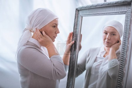 serious sick mature woman in kerchief looking at mirror, cancer concept
