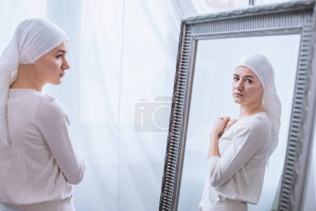 young sick woman in kerchief looking at mirror, cancer concept