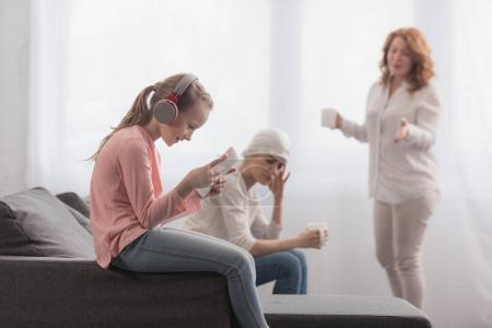 Photo for Child in headphones using digital tablet while sick mother and grandmother talking behind - Royalty Free Image