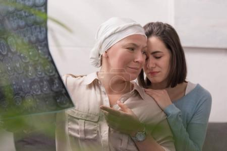 upset crying woman supporting sick mature mother holding mri scan