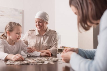 happy family playing with jigsaw puzzle together, cancer concept