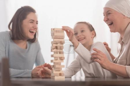 happy family playing with wooden blocks together, cancer concept