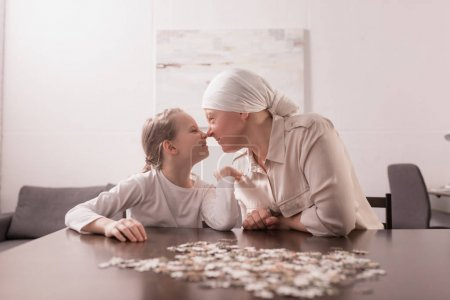 grandmother and granddaughter playing with jigsaw puzzle together, cancer concept